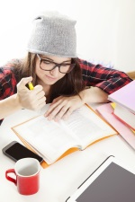 girl in beanie writing in a notebook