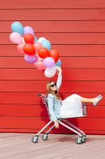 girl sitting in a grocery cart with balloons